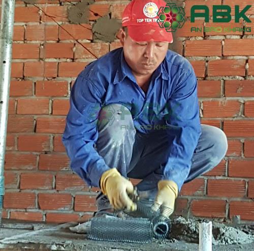Công nhân đóng lưới chống nứt tường